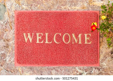 """Welcome Red Mat on grunge stone ."""" Welcome"""" is color gold . Welcome Red Sign."""