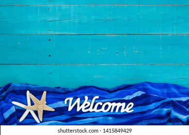 Welcome sign with beach towel and starfish border; vacation background with copy space