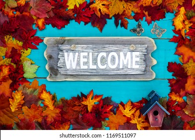Welcome sign with birdhouse, butterflies and colorful fall leaves border hanging on antique rustic teal blue wood door; autumn, Thanksgiving, Halloween, seasonal nature background