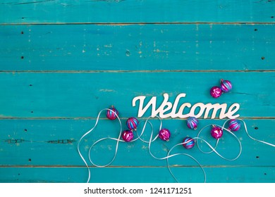 Welcome sign with Christmas ornaments and white ribbon on teal blue rustic wood background; holiday background with copy space
