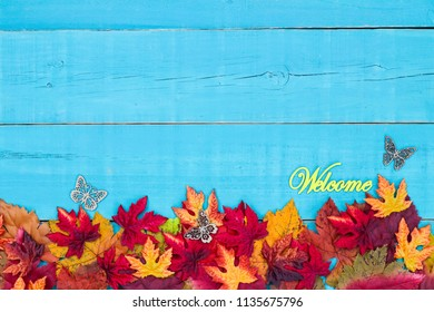 Welcome sign with colorful fall leaves border and butterflies hanging on antique rustic teal blue wood background; autumn, Thanksgiving, Halloween, seasonal nature sign with painted wooden copy space