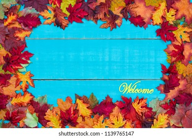 Welcome sign with colorful fall leaves border hanging on antique rustic teal blue wood background; autumn, Thanksgiving, Halloween, seasonal nature sign with painted wooden copy space