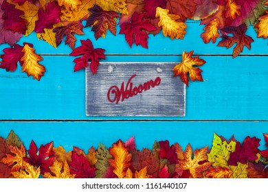 Welcome sign with colorful fall leaves border hanging on antique rustic teal blue wood door; autumn, Thanksgiving, Halloween, seasonal nature background