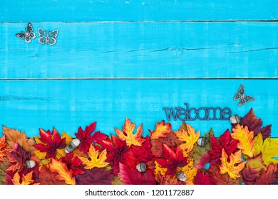 Welcome sign with colorful fall leaves border, butterflies and blank antique rustic teal blue wood background; autumn, Thanksgiving, Halloween, seasonal nature sign with painted wooden copy space
