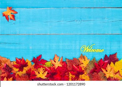 Welcome sign with colorful fall leaves border and blank antique rustic teal blue wood background; autumn, Thanksgiving, Halloween, seasonal nature sign with painted wooden copy space