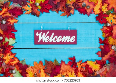 Welcome sign with colorful fall leaves border hanging on antique rustic teal blue wood door; autumn, Thanksgiving, Halloween, seasonal nature background with painted wooden copy space