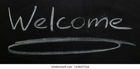 A Welcome sign, drawn on a black board with chalk.