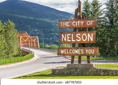 Welcome sign at the entrance of the city of Nelson, BC, Canada - with the West Arm Bridge (Big Orange Bridge) in the background