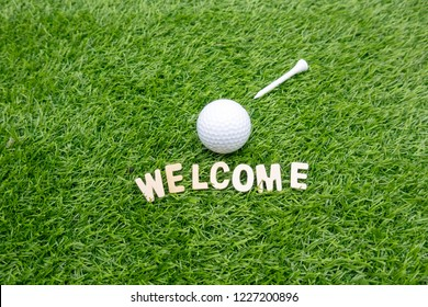 Welcome sign golfer with golf ball on green grass