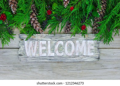 Welcome sign with green Christmas tree garland border, pine cones, and red berries on antique rustic wood door; holiday background