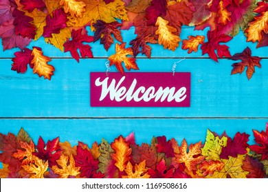 Welcome sign hanging on rustic antique teal blue wood door with colorful fall leaves border; autumn, Thanksgiving or Halloween  background