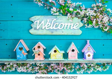 Welcome sign hanging over colorful birdhouses with butterfly on shelf by spring tree flowers on antique rustic teal blue wood background; pink, purple, yellow, orange birdhouses