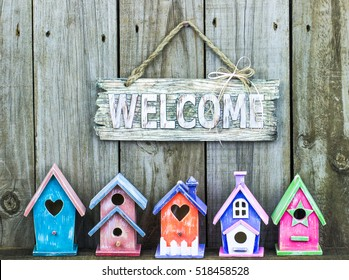 Welcome sign hanging over row of colorful pastel birdhouses with rustic antique wooden background; teal blue, pink, orange, purple and green spring background