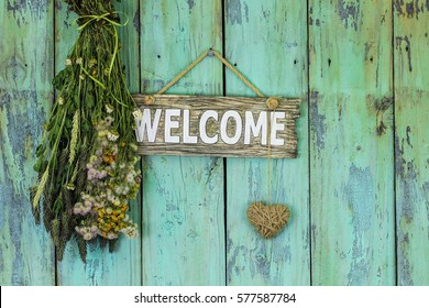 Welcome sign with heart and bouquet of dried meadow flowers hanging by rope on antique rustic teal blue wooden background; Mothers Day, home and love concept background with painted copy space