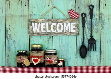 Welcome sign with heart hanging on antique rustic wooden background by cast iron spoon and fork over jelly jars on shelf with red and white checkered fabric; restaurant sign with painted background