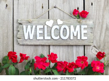 Welcome sign with hearts hanging on rustic wood fence with flower border of red roses