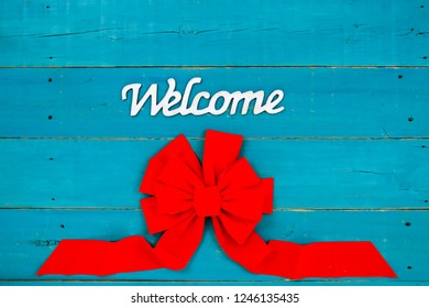Welcome sign with large red Christmas bow hanging on antique rustic teal blue wood door; holiday background with decorations