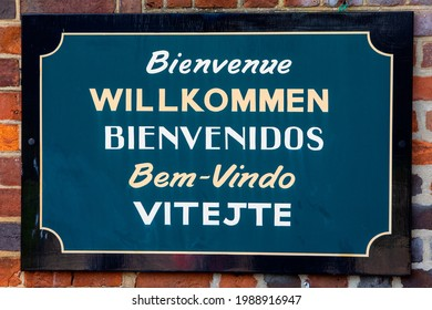 A welcome sign on a building wishing visitors welcome in five different languages - French, German, Spanish, Portuguese, and Czech.