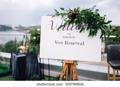 Welcome sign on easel with white frame stands on the roof top during wedding party. Reception. Vow renewal