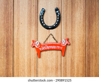 Welcome sign in a shape of dalahast and horseshoe on a door in Dalarna county, Sweden