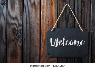 Welcome Sign Written In Chalk On Chalkboard On Rustic Vintage Wood Background. Top View Selective Focus.