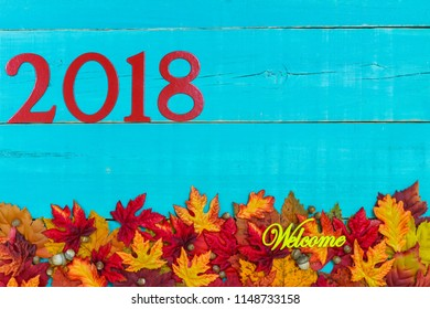 Welcome sign with year 2018 in bold red and colorful autumn leaves border hanging on antique rustic teal blue wood background;  seasonal sign with painted wooden copy space