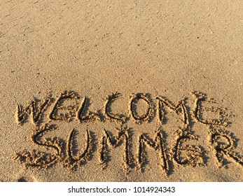 Welcome Summer text on beach sand