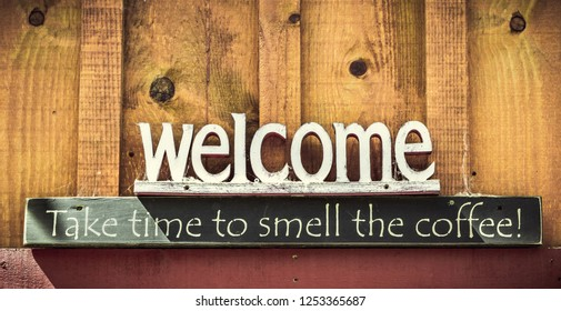 Welcome, Take time tu smell the coffee text sign on a wooden wall with copy space.