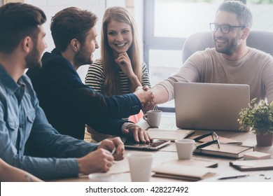 Welcome to team! Two men shaking hands and looking at each other with smile while their coworkers sitting at the business meeting