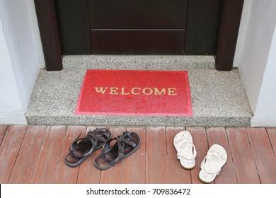welcome text on doormat with shoes in front of door room.