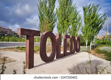 Welcome to Toledo, Spain. Welcome sign at the entrance of the city of Toledo with large letters on the ground and brown. In the background old city on a sunny day with clouds.