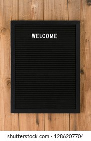Welcome, word written with white plastic letters on felt message board at rustic wooden wall, large copy space
