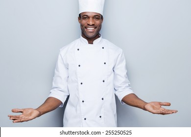 Welcome in the world of tastes. Confident young African chef in white uniform keeping arms outstretched and smiling while standing against grey background