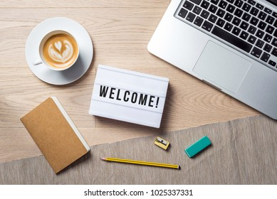 Welcome writing in lightbox lying on wooden desk with office supply and coffee cup as flat lay from bird's eye view