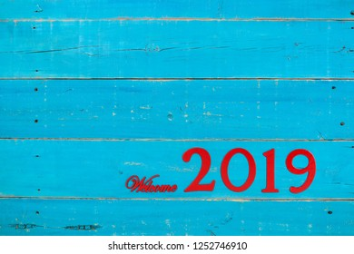 Welcome year 2019 in bold red on blank antique rustic teal blue wood background; message board with New Year holiday concept and painted copy space