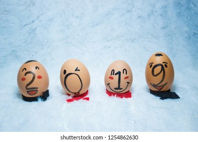 Welcoming 2019 concept design with painted eggs, on top of a white faux fur fabric. Cute/funny faces on eggs. Light blue and yellow/brown opposite/contrasting colors. Concept of friendship.