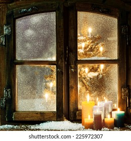 Welcoming Christmas window in a log cabin with a group of burning candles on the windowsill and a glowing Christmas tree visible through the frosted panes