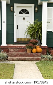 A welcoming entryway with a boston fern, mums and a pumpkin.