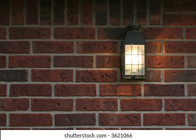 welcoming porch light on brick wall