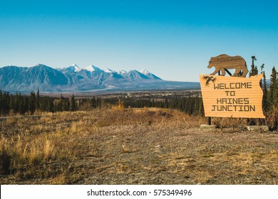 Welcoming sign to Haines Junction in Kluane valley with National Park Kluane in Yukon with a bear on top of the sign and mountains and endless forest behind
