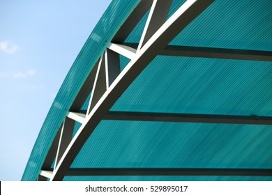 Welded arc polycarbonate canopy against a blue sky in the sunny day