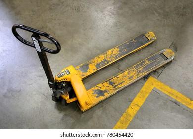Welded steel yellow pallet jack on concrete warehouse floor.