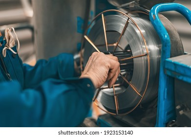The welder adjusts the wire coil to work on the MIG-MAG welding machine. Production of welding works