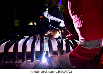 Welder is assembling Hydro-Grate tube to pipe header in the furnace of boiler with Tungsten Inert Gas Welding process. Welder wears protective equipment with a welding mask and heat resistant gloves.