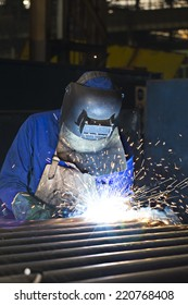 Welder busy joining a piece of metal, wearing protective gear
