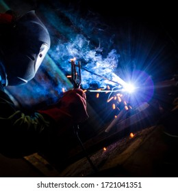 welder doing metal work at night, front and background blurred with bokeh effect