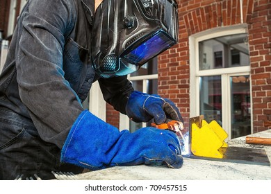 A welder, dressed in black work clothes, in a black welding mask and blue protective gloves, welds metal with welding machine in the street, in the background - a brick old wall