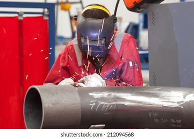 welder in factory with protective equipment welding pipe