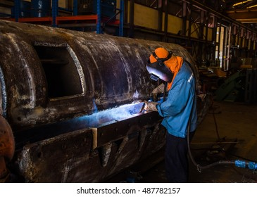 Welder with Flux Core Arc Welding process inside steel structure weld repair in fabrication factory.