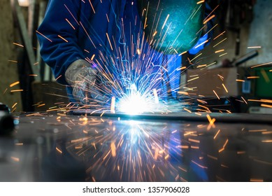 Welder in his workshop welding metal, lots of sparks flying around
